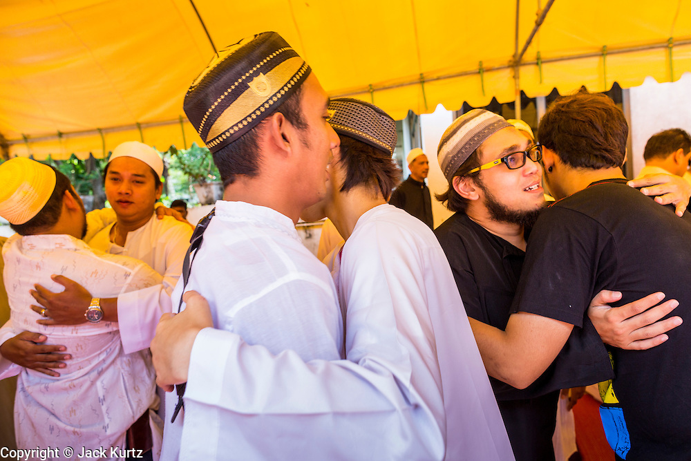 "08 AUGUST 2013 - BANGKOK, THAILAND: Men greet each other after Eid al-Fitr services at Haroon Mosque in Bangkok. Eid al-Fitr is the ""festival of breaking of the fast,"" it's also called the Lesser Eid. It's an important religious holiday celebrated by Muslims worldwide that marks the end of Ramadan, the Islamic holy month of fasting. The religious Eid is a single day and Muslims are not permitted to fast that day. The holiday celebrates the conclusion of the 29 or 30 days of dawn-to-sunset fasting during the entire month of Ramadan. This is a day when Muslims around the world show a common goal of unity. The date for the start of any lunar Hijri month varies based on the observation of new moon by local religious authorities, so the exact day of celebration varies by locality.       PHOTO BY JACK KURTZ"