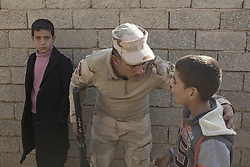 November 11, 2016 - Mosul, Nineveh, Iraq - 11/11/2016. Mosul, Iraq. A soldiers, belonging to the Iraqi Army's 9th Armoured Division, talks to a young boy who is asking for food during a visit to Mosul's Hay Intisar district on the south east of the city. The district was taken by Iraqi Security Forces (ISF) around a week ago and, despite its proximity to ongoing fighting between ISF and ISIS militants, many residents still live in the settlement...The battle to retake Mosul, which fell June 2014, started on the 16th of October 2016 with Iraqi Security Forces eventually reaching the city on the 1st of November. Since then elements of the Iraq Army and Police have succeeded in pushing into the city and retaking several neighbourhoods allowing civilians living there to be evacuated - though many more remain trapped within Mosul. (Credit Image: © Matt Cetti-Roberts via ZUMA Wire)