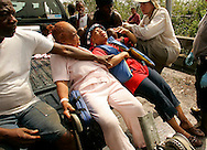 Gwendolyn Martin Washington (R) lies in the back of a pickup truck with her mother Rosemary Martin (C) and brother Micahel (L) as they are evacuated from a flooded area in New Orleans August 30, 2005. The historic city of New Orleans was steadily filling with water from nearby Lake Ponchartrain on Tuesday after its defenses were breached by the ferocity of hurricane Katrina.