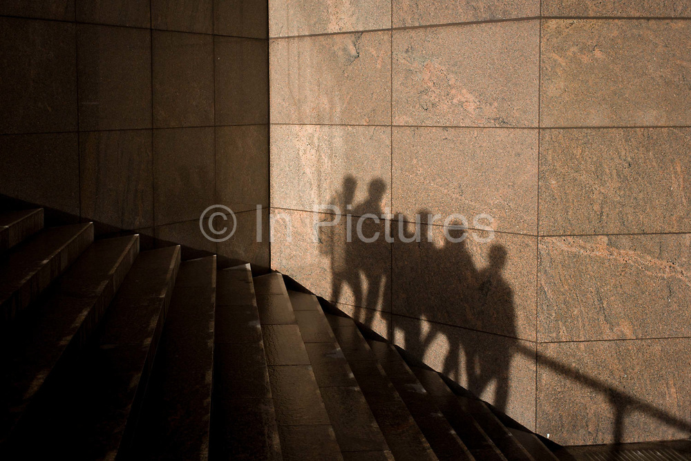 The shadows of anonymous people are seen on a wall in Southwark, on the south side of London Bridge. The group walk together in one direction, seen as silhouetted figures, we see their shape and form against the constructed modern wall of an office development on the southern side of London Bridge in the borough of Southwark.
