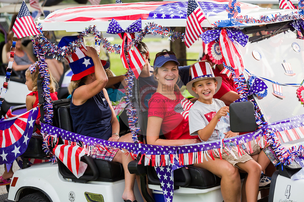 A family rides in their golf cart decorated with bunting and American flags during the Daniel Island Independence Day parade July 3, 2015 in Charleston, South Carolina.