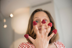 Pregnant woman holding raspberry on her fingers in the kitchen, Munich, Bavaria, Germany