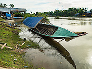 21 JUNE 2016 - DON KHONE, CHAMPASAK, LAOS: A tourist boat rest on its side in the Mekong River on Don Khone Island. Don Khone Island, one of the larger islands in the 4,000 Islands chain on the Mekong River in southern Laos. The island has become a backpacker hot spot, there are lots of guest houses and small restaurants on the north end of the island.       PHOTO BY JACK KURTZ