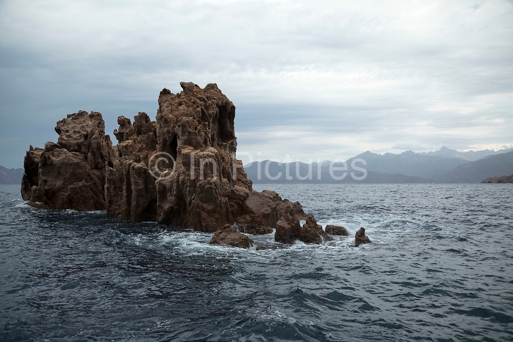 Mountain landscape of the Calanques de Piana, gold and pink coloured granite rock formations formed by wind and rain erosion creating dramatic cavities as they descend into the sea at the gulf of Porto on 15th September 2017 in  Corsica, France. Corsica is an island in the Mediterranean and one of the 18 regions of France. It is located southeast of the French mainland and west of the Italian Peninsula.