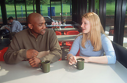 Teenage girl and boy sitting at table in café talking,