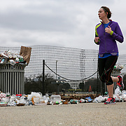 A runner passes by overfilled trashcans at the Washington Monument during the partial government shutdown on Wednesday, January 2, 2019.