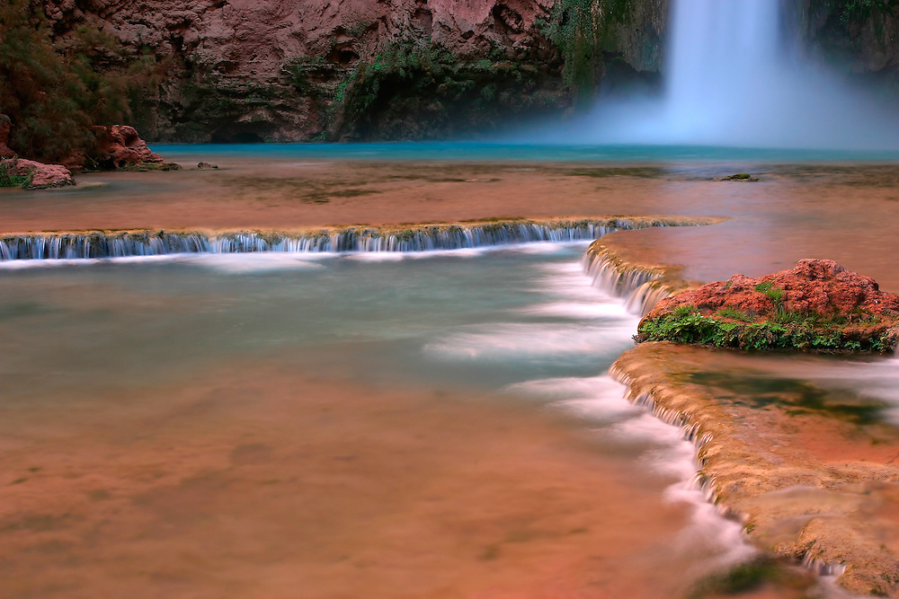 """Mooney Falls is a waterfall on Havasu Creek, in the northwest corner of the U.S. state of Arizona, near the town of Supai in the Havasupai Indian Reservation. It is named after prospector D. W. """"James"""" Mooney who fell to his death trying to cross the canyon on a homemade ladder. Local Native Americans called it """"Hualapai"""" or """"Hualpai"""" falls. It is located about 1 kilometre downstream (i.e. to the north) of Havasu Falls, just past the large campground that lies between the two falls. Mooney Falls is accessible with considerable difficulty down a very steep trail (including two rock tunnels) that has been cut into the rock. Chains and a ladder at the bottom assist, but spray from the falls coats the dust-covered rock with water and reddish mud that makes climbing treacherous."""
