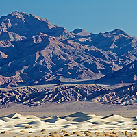 Arid, eroded Grapevine Mountains rise above Mesquite Sand Dunes in California's Death Valley National Park.