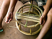 A Tai Lue man makes a stool from rattan and bamboo, Ban Ngay Neua village, Phongsaly province, Lao PDR. One of the most ethnically diverse countries in Southeast Asia, Laos has 49 officially recognised ethnic groups although there are many more self-identified and sub groups. These groups are distinguished by their own customs, beliefs and rituals.