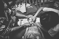 Namfon, aged 6, suffers from Japanese Encephalitis at a hospital in Vientiane, Laos. Her father and mother massage her joints and limbs to help ease her pain.
