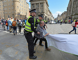 Pictured: Police remove a protester who had attempted to block the road.<br /> <br /> Climate change protesters blocked roads in the city centre including North Bridge, causing severe traffic disruption.<br /> <br /> © Dave Johnston / EEm