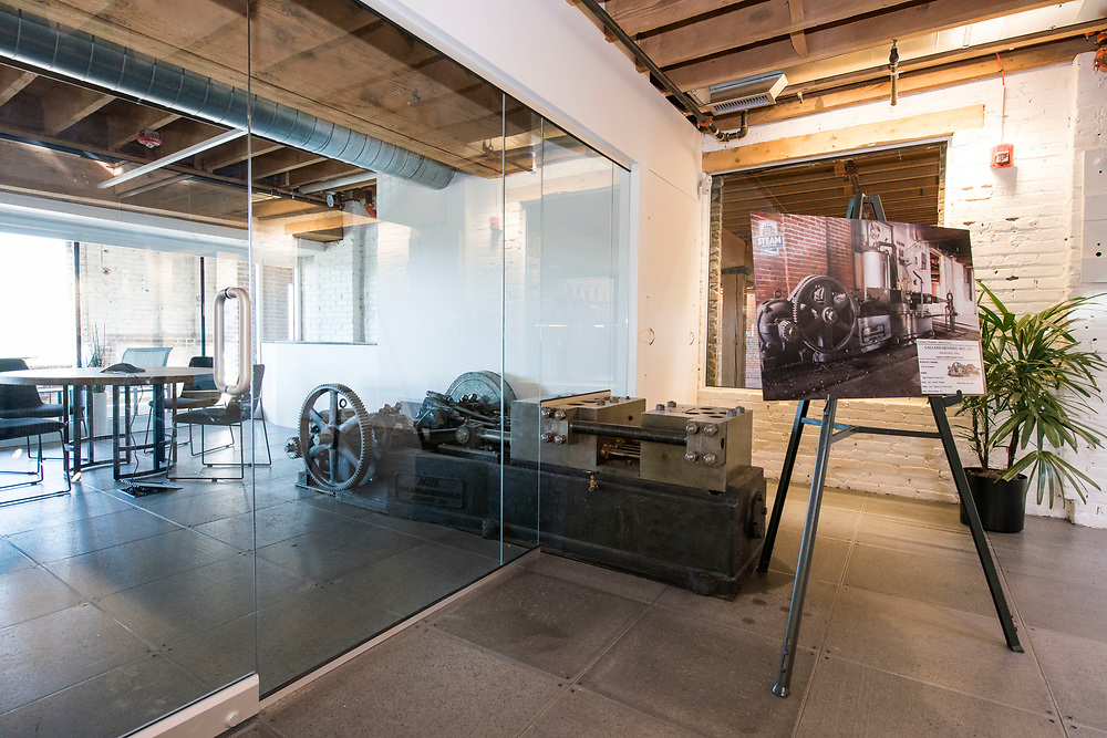 DENVER – NOV. 3. A modern conference room shares its floorplan with a disused industrial hydraulic pump inside STEAM on the Platte, a newly redeveloped historic reuse space at West 14th Avenue and Zuni Street in Denver's Sun Valley neighborhood. The pump and a nearby hydraulic textile baling machine are fixtures of the building's industrial heritage. (Photo by Andy Colwell/Special to The Denver Post)