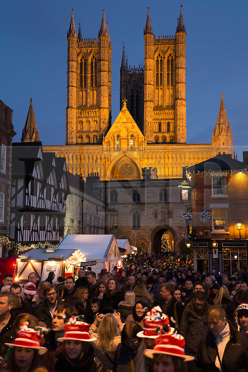"""© Licensed to London News Pictures. 7/12/2013. Lincoln, UK. Lincoln City Centre was packed with Christmas shoppers this weekend. Pictured, The floodlit Lincoln Cathedral stands proud as the Christmas market shoppers throng in the market square below. Thousands of shoppers filled the City Centre and stewards were called in to direct people up the narrow """"Steep Hill"""" towards the upper area of Lincoln near the Cathedral. The Christmas Market now in it's 31st year with over 250 stalls attracts people from abroad as well as UK visitors. Photo credit : Dave Warren/LNP"""