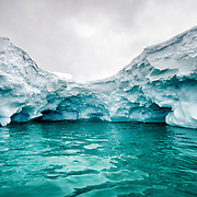 A shot from within a small cover created by an iceberg, with the green of the underwater segment of the iceberg in the foreground. Curtis Bay, Antarctica.