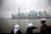 A family of Muslim Hui minorities look at Pudong's skyscrapers shrouded in clouds while standing on the Bund in Shanghai, China on 9 May 2010.