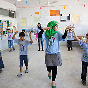 In Ein El-Hilweh refugee camp, home to 75.000 Palestinians. Boys practise run a dance play. It is summer break in the UNWRA school and Naba'a runs Play and Learn sessions in the empty school for vulnerable children. They aim is to give them a safe space to express themselves with out fear of repression. Developmental Action Without Borders(Naba'a) work in Palestinian refugee camps across Lebanon to help children in the camps.  The camps are densely over-crowded and many of the children are 4th generation refugees living in Lebanon with no citizenship or rights and under immense pressure. Naba'a is a mix of Palestinians and Lebanese and aim to give children a sense of security and freedom to express their needs and rights.Naba'a operates in communities governed by a multitude of political parties and religious groups and Naba'a keeps a strict independed line from any affiliation with any groups.