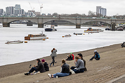 """© Licensed to London News Pictures. 28/03/2021. London, UK. Members of the public enjoy relax along the River Thames in Putney, South West London ahead of the end of the """"Stay at Home"""" advice from tomorrow with temperatures expecting to reach up to 23c next week. On Monday 29 March, the """"Stay at Home"""" advice will end with people being allowed to meet up within the """"rule of six"""". Playing golf, tennis and organised outdoor sports will also be allowed as England starts to unlock after a year of Covid-19 restrictions. Photo credit: Alex Lentati/LNP"""