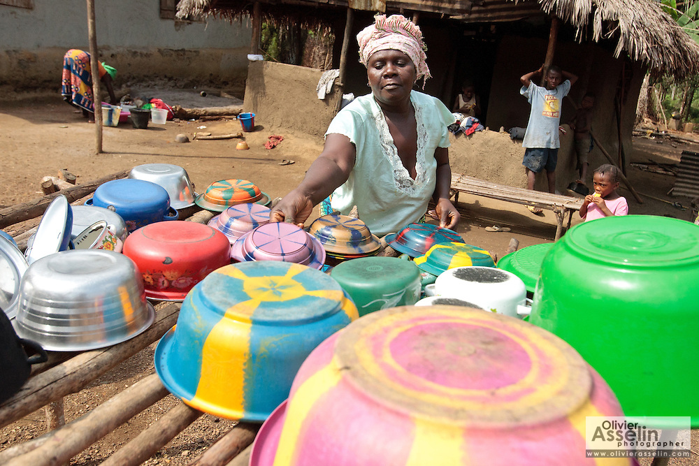 A woman sets bowls, pots and dishes on an elevated dish rack, used to dry dishes instead laying them directly on the ground, outside her home in the village of Kawejah, Grand Cape Mount county, Liberia on Friday April 6, 2012. As part of the UNICEF-sponsored CLTS (community-led total sanitation) programme, such racks are built by families to help improve hygiene conditions and prevent the spread of diseases.