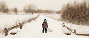 A boy stands with a sled on a snowy road in northern Michigan.