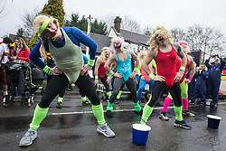 Windlesham, UK. 26 December, 2019. Competitors entertain spectators with a dance as they take part in the annual fancy dress Windlesham Boxing Day Pram Race charity event along a 3.5-mile course through Windlesham village with stops at local pubs along the route.