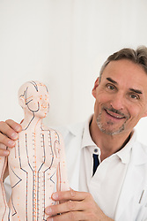 Male doctor showing anatomical model and smiling, Munich, Bavaria, Germany