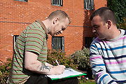 Two prisoners studying in the grounds of the prison writing. HMP The Mount, Bovingdon, Hertfordshire