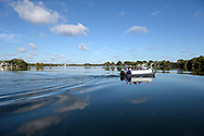 People riding on the Scenic Boat Tour glide across the water on Lake Maitland in Winter Park, Fla., Friday, Oct. 30, 2015. (Phelan M. Ebenhack via AP)