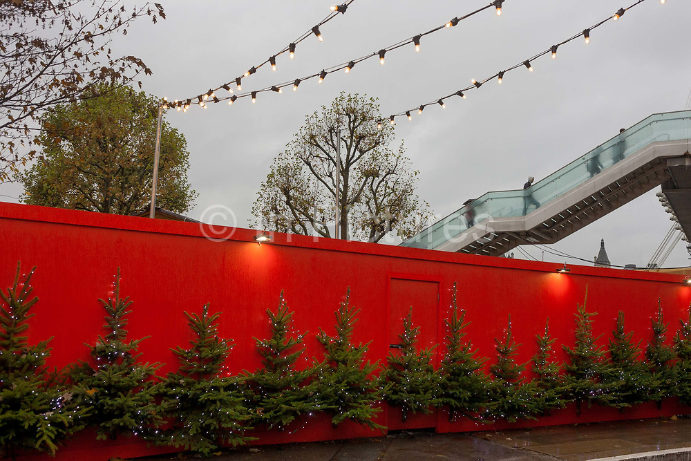 Christmas trees attached to a red hoarding near an Xmas theme village on Londons Southbank, on 21st November 2016, London, England.