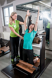 Fitness trainer helping mature woman stretching