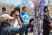 "Brooklyn, NY - 17 April 2016. Two young women examine the offerings of a seller of political pins as they wait to get into the rally. Vermont Senator Bernie Sanders, who is running as a Democrat in the U.S. Presidential primary elections, held a campaign ""get out the  vote"" rally in Brooklyn's Prospect Park."