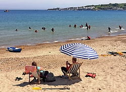 © Licensed to London News Pictures. 22/05/2019. Dorset, UK. A group of young people take part in activities in the sea as people relax on deck chairs on the beach in Swanage Bay on a hot sunny day in Dorset, UK. Photo credit: LNP