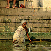 Asia, India, Varanasi. A woman takes a dip in the sacred Ganges River.