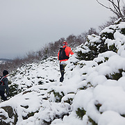 A runner makes his way across the snowy and hilly landscape.  Salomon Hammer Trail Winter Edition is a first on Bornholm and is one of the toughest routes in Denmark. The 4 runs consist of a 50 mile run, a marathon, a 1/2 marathon and 10k all run a on an approximate 25km route which includes 860 meter vertical rise on the North East coast of the Danish island Bornholm. The cut-off time for the 50mile run was 16 hours and more than a hundred runners made it to the finishing line. The last runner across the line after 50 miles  was in after 15:14:40