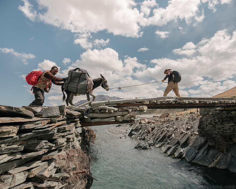 """Crossing the Wakhan river in Bozoi Gumbaz, near the source of the Amu Darya, also known as the Oxus. Most of the time we ford river on foot – here one of the rare bridge and one of our donkey hated it, took us 20 minutes to get him over. Donkey work is hard work, you often have to scream to get the donkey going, the load slides on the side etc . On the way from Aqbelis pass to Baiqara, a Wakhi high pasture. Guiding and photographing Paul Salopek while trekking with 2 donkeys across the """"Roof of the World"""", through the Afghan Pamir and Hindukush mountains, into Pakistan and the Karakoram mountains of the Greater Western Himalaya."""