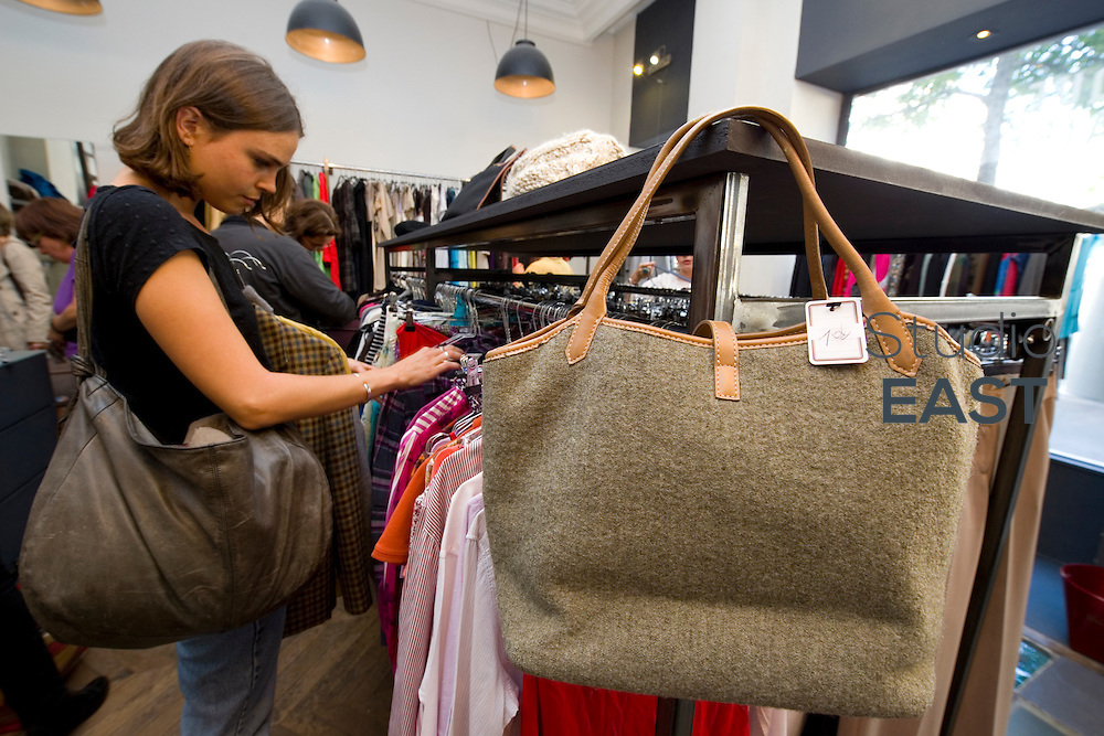 PARIS, FRANCE - SEPTEMBER 20: Elsa Nero looks for second hand clothes in BIS store, where a handbag is only 10 euros, on September 24, 2013, in Paris, France. Despite its airy, New York loft style interior, Bis store is a second hand store that offers reasonably priced used clothing in a chic and contemporary setting. (Photo by Lucas Schifres/Getty Images)