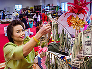 14 APRIL 2019 - DES MOINES, IOWA: A woman puts dollar bills on a money tree which will be donated to the temple during Lao New Year, also called Songkran,  observances at Wat Lao Buddhavath in Des Moines. Several thousand Lao people live in Des Moines. Most came to the US after the wars in Southeast Asia. Songkran is celebrated in Theravada Buddhist countries (Sri Lanka, Myanmar, Thailand, Laos, and Cambodia) and in Theravada Buddhist communities around the world.        PHOTO BY JACK KURTZ