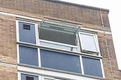 A window in a top floor flat remains wide open while below a police tent covers the spot where a woman in her 20s was found injured outside the Brookbank Tower in Enfield, North London, and declared dead at the scene. According to a local resident the woman had fallen from a top floor flat in the tower black. A man was arrested nearby on suspicion of murder. . London, April 08 2019.