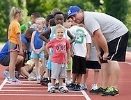 Middletown High School track coach Eric Hipsman, at right, and Noah Freestone, 3, look down the runway at the Middletown High School track before Noah long jumps during the Twilight Track and Field Series on Tuesday, July 30, 2013.