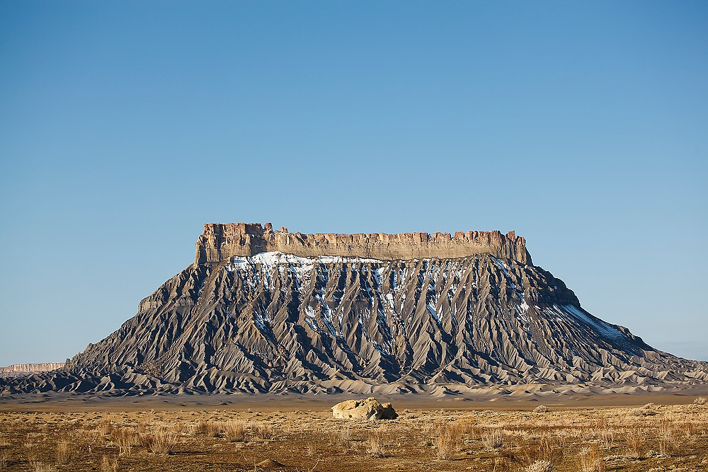 Factory Butte stands amidst mancos shale badlands near Hanksville, Utah.