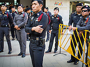 """14 FEBRUARY 2015 - BANGKOK, THAILAND:  Thai police watch protestors Saturday. Dozens of people gathered in front of the Bangkok Art and Culture Centre in Bangkok Saturday to hand out red roses and copies of George Orwell's """"1984."""" Protestors said they didn't support either Red Shirts or Yellow Shirts but wanted a return of democracy in Thailand. The protest was the largest protest since June 2014, against the military government of General Prayuth Chan-Ocha, who staged the coup against the elected government. Police made several arrests Saturday afternoon but the protest was not violent.     PHOTO BY JACK KURTZ"""