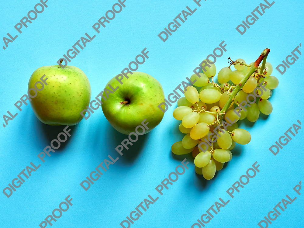 Above view of isolated set of a green apple with a bunch of sweet seedless grapes in studio with blue background