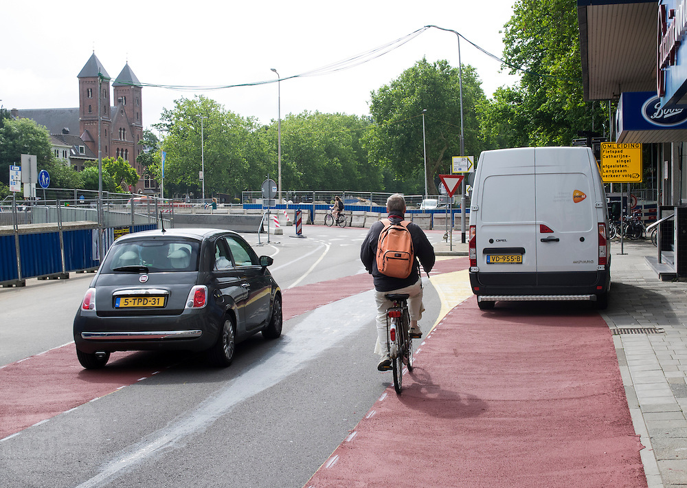 In Utrecht heeft een pakketbezorger van PostNL de auto op een fietsstrook gezet, waardoor fietsers moeten uitwijken.<br /> <br /> In Utrecht a post man of PostNL parked his van on the bicycle path, blocking the way for cyclists.