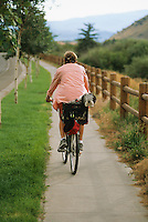 A young woman rides a cruiser bike with her dog in the town of Jackson, Wyoming.