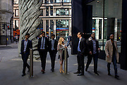 City workers pass-by the giant artwork of a bronze wing<br /> during lunchtime in London's financial district. As light reflects off nearby office buildings, the lunchtime crowd walk past this giant artwork on their way to meetings and sandwich bars. The ten-metre-tall bronze sculpture is by President of the Royal Academy of Arts, Christopher Le Brun, commissioned by Hammerson in 2009. It is called 'The City Wing' and has been cast by Morris Singer Art Founders, reputedly the oldest fine art foundry in the world.