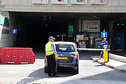 Israel, Haifa, A parking lot. Security guard inspects car before entering the building