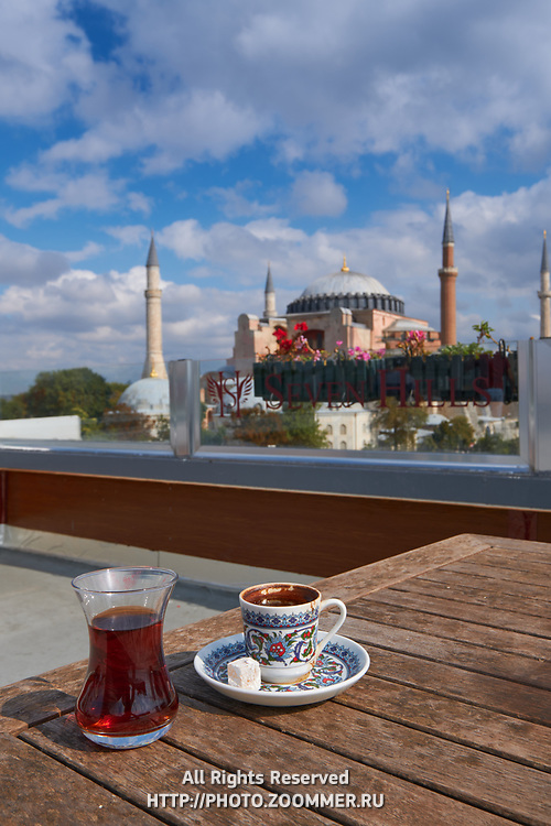 Traditional turkish tea and coffee on a table of Seven Hills cafe, Hagia Sophia mosque on background, Istanbul