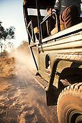 A 4x4 drives along a dirt road in the Okavango Delta, Botswana