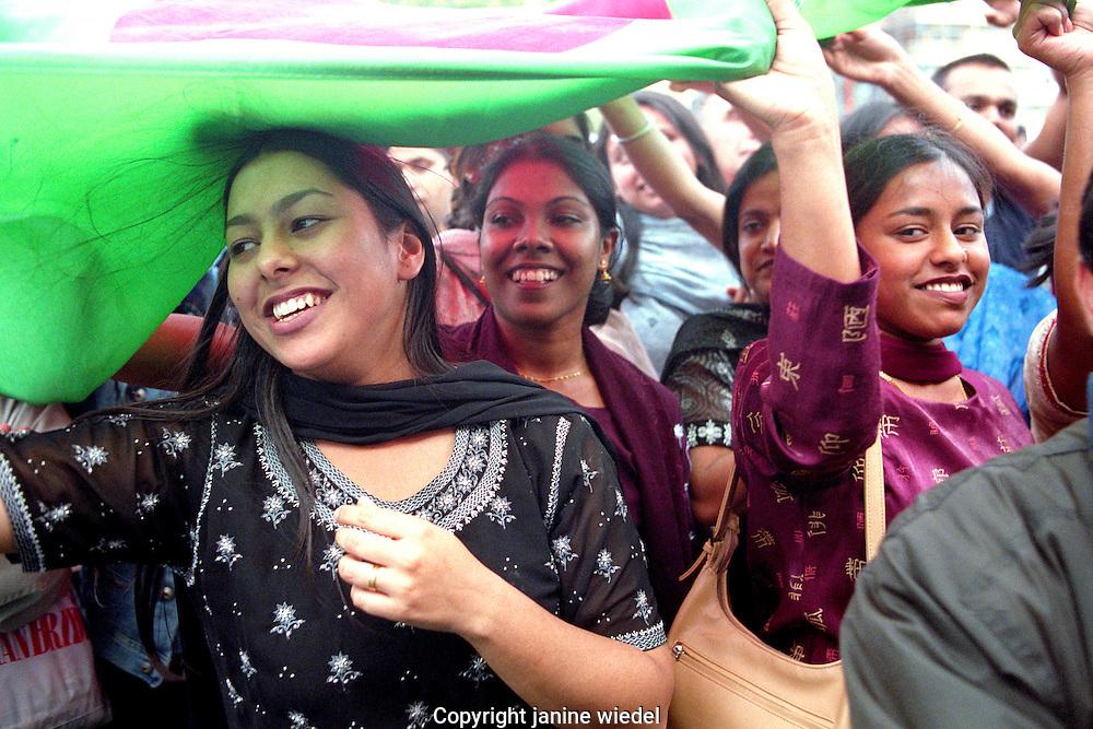 Women and men dancing at annual Brick Lane Bangladeshi  Festival  in East london.