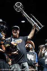 After the 2018 National Champion Andy DiBrino wrecked in the last Hooligan race of the season and ended up in the hospital, his father had to go onto the Surf City Blitz stage to accept his trophy and the big prize, the first Roland Sands custom FTR 1200 Indian during the RSD Moto Beach Classic award ceremony on the main Surf City Blitz stage. Huntington Beach, CA, USA. Sunday October 28, 2018. Photography ©2018 Michael Lichter.
