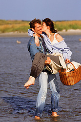 man carrying a woman in shallow water at Jones Beach, NY